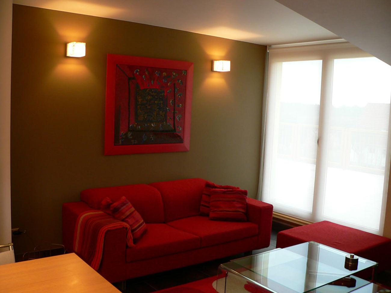 Sedací souprava se stejně barevným rámem osobního obrazu majitelky a kontrastně laděná stěna.